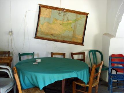 τραπ�ζι για χαρτοπαιξία, παραδοσιακ�ς και πλαστικ�ς καρ�κλες κι ο χάρτης της Κύπρου �χοντας απωλ�σει την ισορροπία του